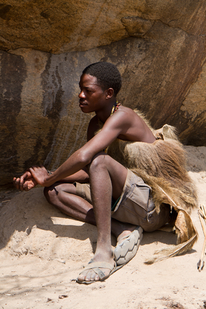 hunter gatherer: hadzabe tribe young man relaxing in the sun Editorial