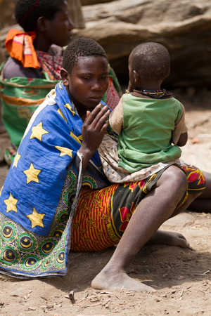 hunter gatherer: hadzabe mother with her son in tanzania