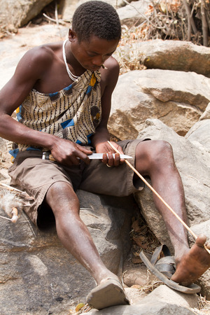 hadzabe tribe, young man making an arrow Editorial