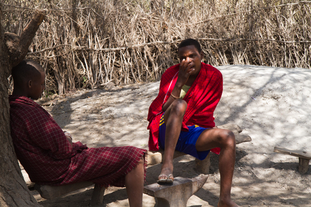 hunter gatherer: datoga tribe two man sitting together in the shade Editorial