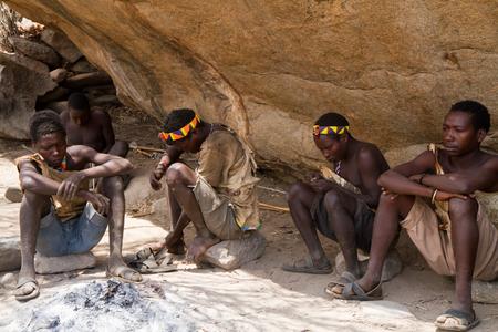 hunter gatherer: hadzabe man sitting around the fire in a village in tanzania
