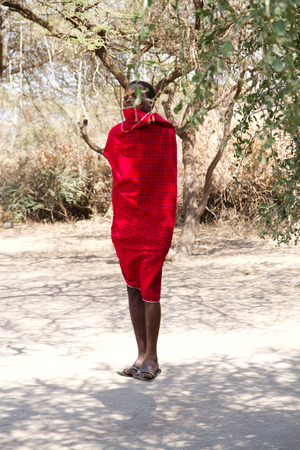 hunter gatherer: datonga tribe, boy jumping in his red typical dress
