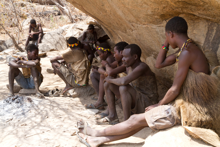hunter gatherer: hadzabe tribesmen sitting in the shade in tanzania Editorial