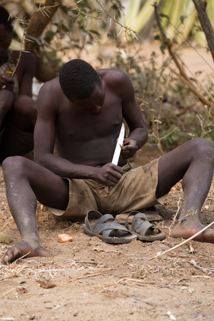 hunter gatherer: hadzabe tribe, man cutting a branch to make a arrow