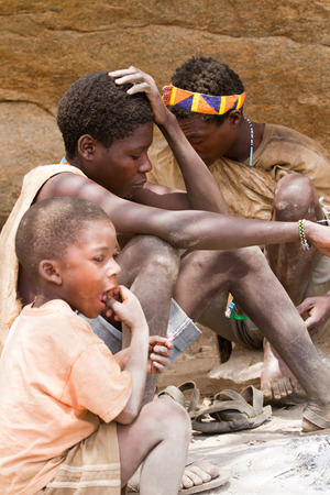 hunter gatherer: hadzabe tribe, men sitting in the shade in hot day Editorial