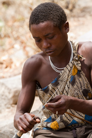 hunter gatherer: hadzabe tribesman cutting the arrow used to hunt