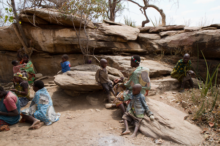 hunter gatherer: hadzabe tribe sitting together in the village