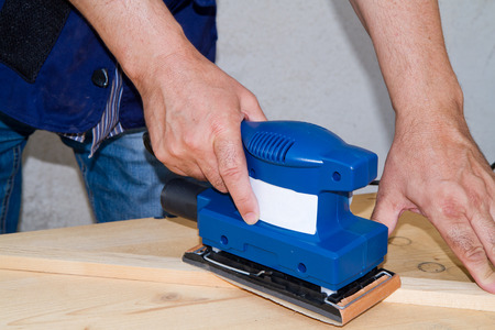 sanding block: smoothing a piece of wood for furniture
