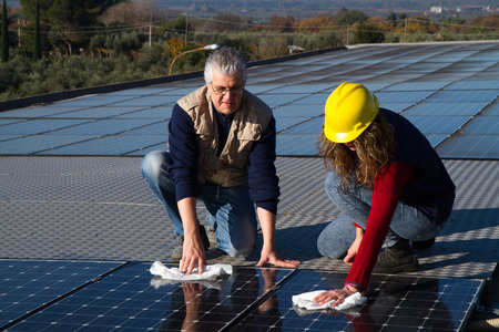 young girl and elderly man cleaning photovoltaic panels Stock Photo