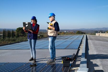 young engineer girl and an elderly skilled worker fitting a photovoltaic plant photo