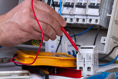 electrician fixing  electrical devices with different tools