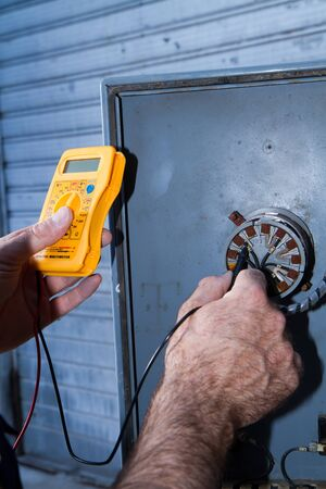 electrician at work with an electric panel Stock Photo