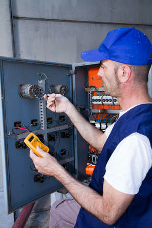 electrician at work with an electric panel Banque d'images