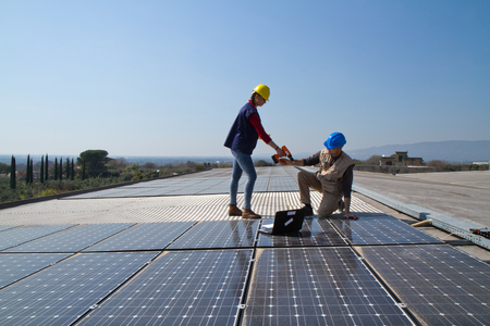 young engineer girl and an elderly skilled worker fitting a photovoltaic plant Фото со стока