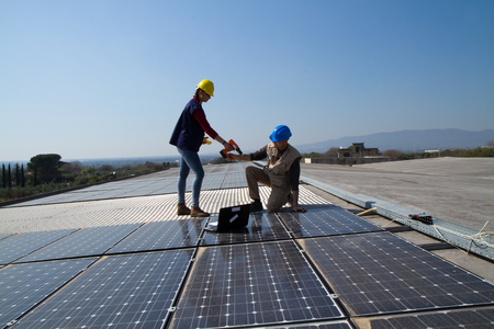 young engineer girl and an elderly skilled worker fitting a photovoltaic plant Standard-Bild - 113789481