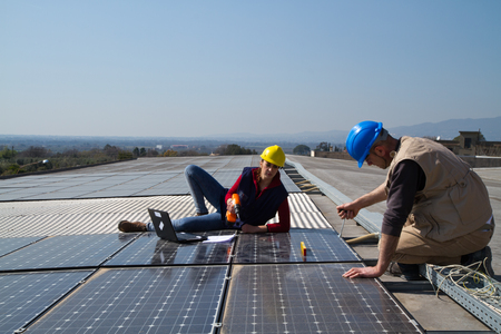 young engineer girl and an elderly skilled worker fitting a photovoltaic plant Stock Photo