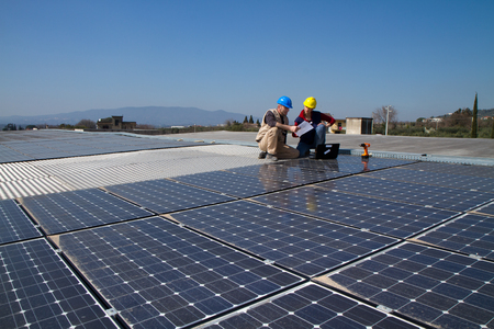 young engineer girl and an elderly skilled worker fitting a photovoltaic plant Standard-Bild - 113789431