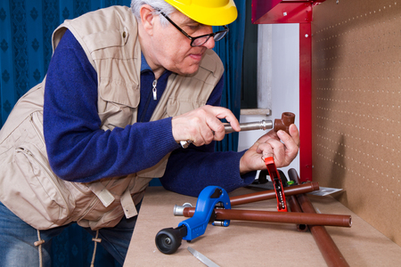 plumber at work on his workbench to fix pipes