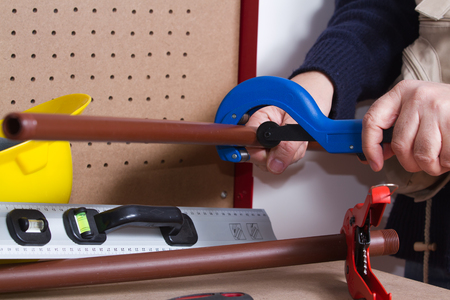 plumber at work on his workbench to fit pipes Stock Photo