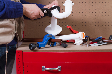plumber at work on his workbench to fit pipes Standard-Bild - 113789409