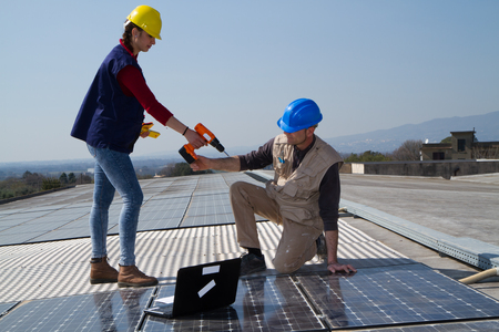 young engineer girl and an elderly skilled worker fitting a photovoltaic plant Standard-Bild - 113789415
