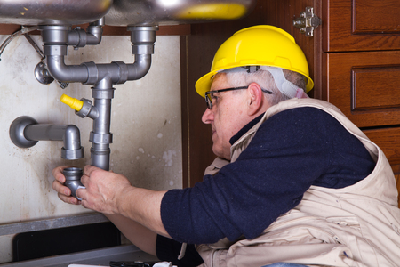 plumber at work to fix a sink Stock Photo