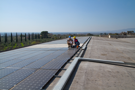 young engineer girl and an elderly skilled worker fitting a photovoltaic plant Standard-Bild - 113789383