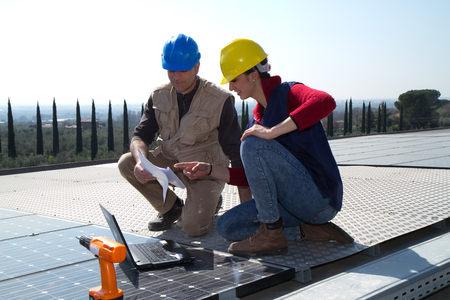 young engineer girl and an elderly skilled worker fitting a photovoltaic plant Standard-Bild - 113789388