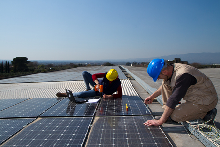 young engineer girl and an elderly skilled worker fitting a photovoltaic plant Standard-Bild - 113789390