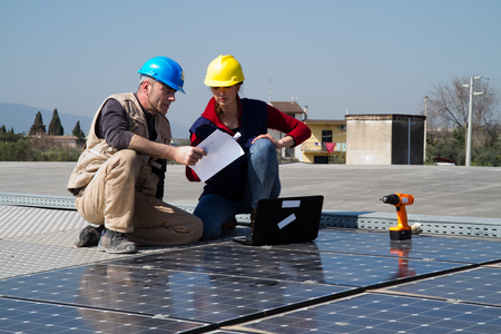 young engineer girl and an elderly skilled worker fitting a photovoltaic plant Standard-Bild - 113789348