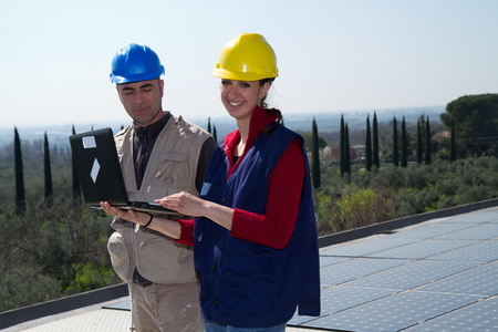 young engineer girl and an elderly skilled worker fitting a photovoltaic plant Standard-Bild - 113789350
