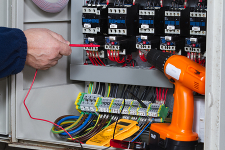 electrician at work with an electric panel Stockfoto
