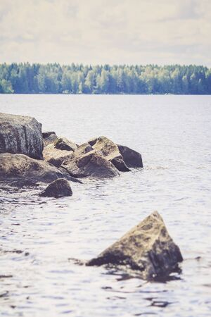 Huge calm blue summer lake with green taiga forest in background and big solid rocks on front