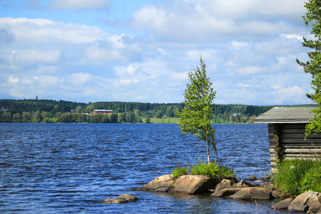 ness river: Windy summer day on huge clear blue lake with birch on  rocky headland in front with little old wooden boathouse and green taiga forest in background horizon Stock Photo