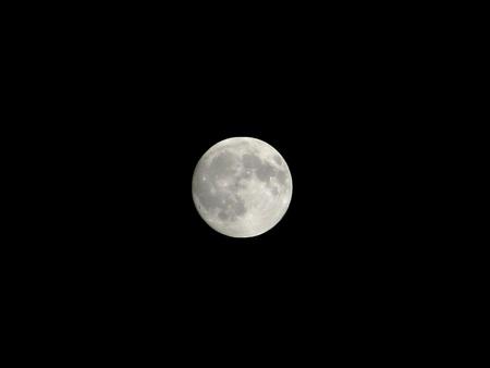 The moon isolated in dark sky photo