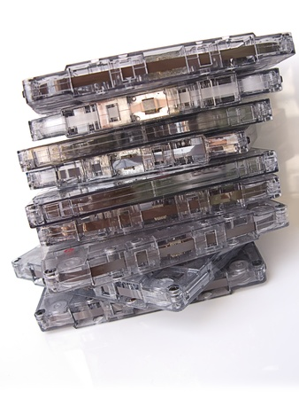 A pile of old fashioned cassette tapes, isolated in white photo