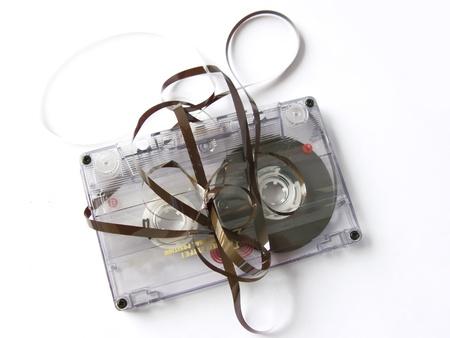 Une vieille endommagé audiocassette, isolé en noir. Technologie reste de vieux eighties