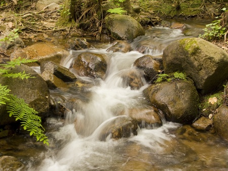 Beautiful waterfall in the rocks. Fresh and clean little river, a relaxing place in the mountain photo