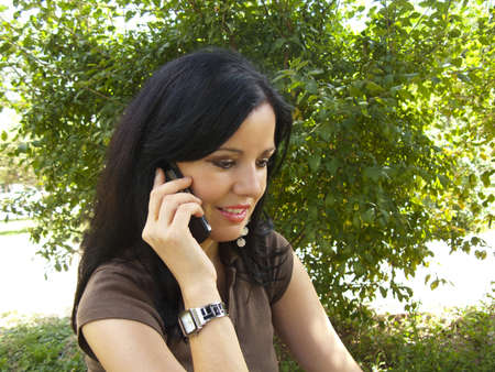 Beautiful young brunette woman talking on her mobile phone at the garden Stock Photo - 9936491