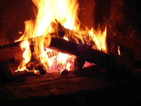 Warming fireplace in winter, at home. Close up of flames and firewood photo