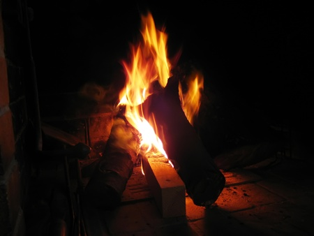 Warming fireplace in winter, at home. Close up of flames and firewood Stock Photo