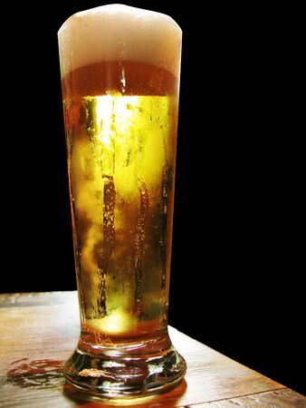 amber light: Cold and fresh beer isolated in black