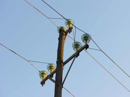 Electric posts over blue sky, detail photo