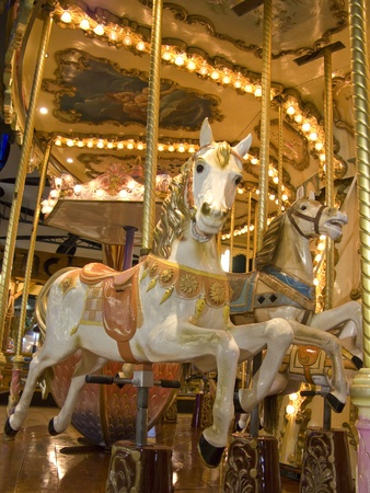 carousel: An old fashioned carousel at night. Detail of two horses