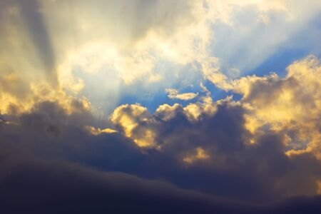 Dramatic sunset with golden sun rays among the clouds photo