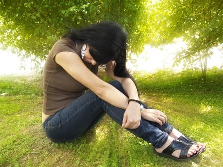 ragazza depressa: Depresso giovane donna in giardino