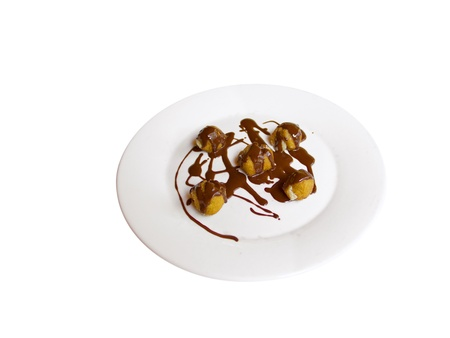 A plate with profiteroles and chocolat  Isolated in White photo