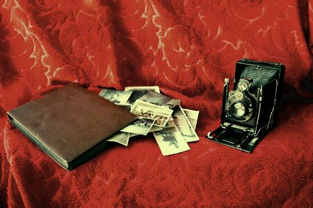 Una cámara muy vieja desde el comienzo de la serie siglo XX con un viejo álbum, fotografías antiguas y alguna película más de efectos de fondo, retro, hizo como que se trataba de una fotografía muy antigua Foto de archivo - 13177408