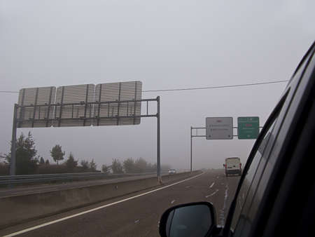 Driving a car in the road with a heavy fog. Some place in Spain during the autumn photo