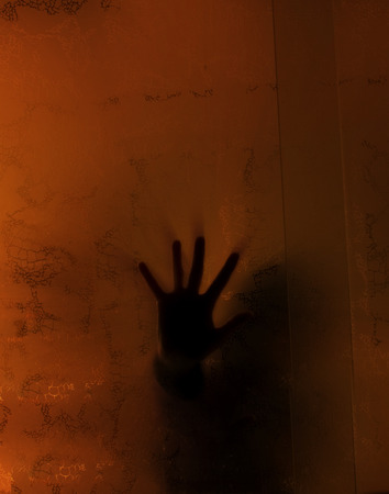Spooky hand behind a glass in an abandoned house photo